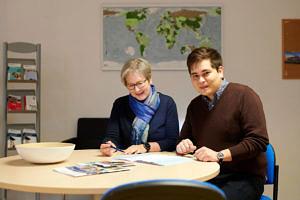 Zwei Personen bei einer Beratung an einem Schreibtisch.